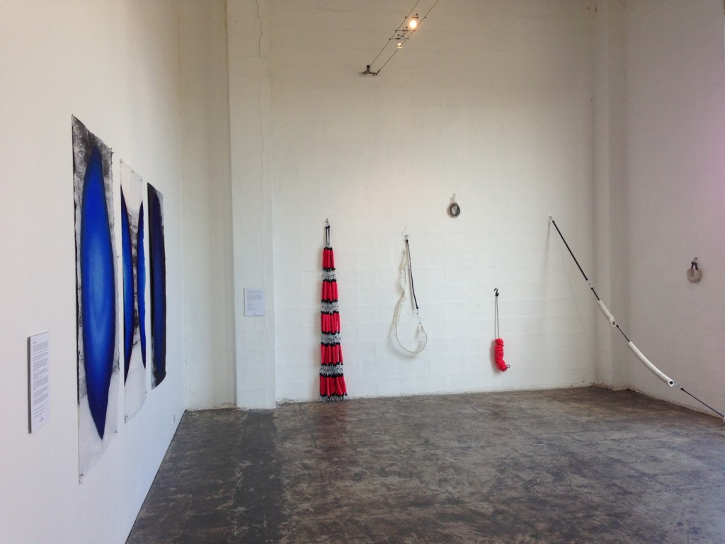 Installation View of quietNOISE, on the right Caroline Phillips, Lug, rubber octopus straps, chenille stems, 198 x 33 x 12 cm, 2013. Equilibrium, rubber octopus strap, wire, plastic and rubber, 145 x 45 x 10 cm, 2013. Untitled, recycled rubber, cotton elastic, 25 x 15 x 10 cm, 2013. Skulk, recycled leather, synthetic tie-down strap, 95 x 15 x 12 cm, 2013. Suspension No.2, rubber octopus straps, recycled rubber, Length 530 cm, dimensions variable, 2013. Suspension No.3, rubber octopus straps, recycled rubber, 25 x 16 x 5 cm, 2014.